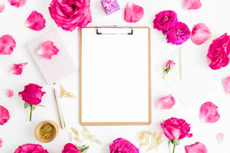 Composition with clipboard, notebook, roses flowers and accessories on white background. Flat lay, top view.