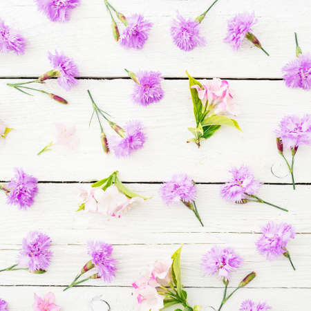Floral pattern made of pink flowers and leaves on wooden rustic background. Flat lay, top view.