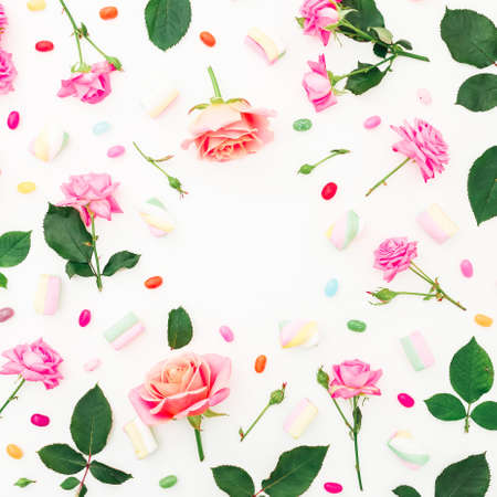 Roses flowers and marshmallow with candy on white background. Flat lay, top view. Zdjęcie Seryjne