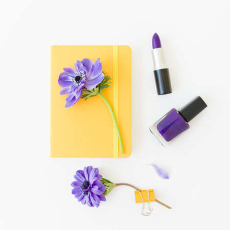 Beauty composition with yellow notebook, anemones and nail polish on white background. Flat lay.