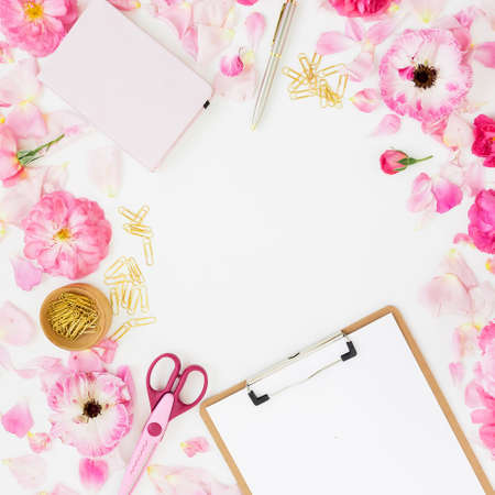 Stylish frame workspace with clipboard, notebook, pink flowers and accessories on white background. Flat lay, top view.