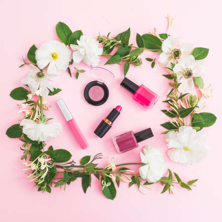 Beauty composition with flowers and make up cosmetics on pink background. Top view. Flat lay