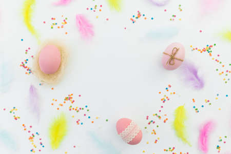 Ester frame composition with colorful eggs, feathers and confetti on white background. Flat lay, top view