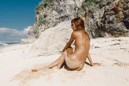 Naked woman with towel at tropical beach. Nude caucasian girl