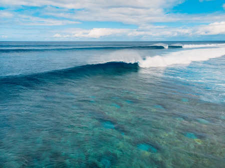 Blue barrel wave in tropical ocean. Aerial view of ideal surfing waves