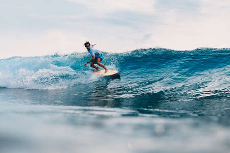 March 11, 2021. Bali, Indonesia. Surfer on surfboard and blue wave. Woman in ocean during surfing.