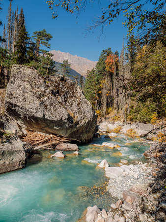 High mountain landscape with river. Rocks, mountains and autumnal trees. Banco de Imagens