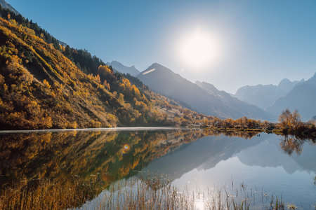 Mountain lake with reflection, autumnal trees. Lake with sun and mountains
