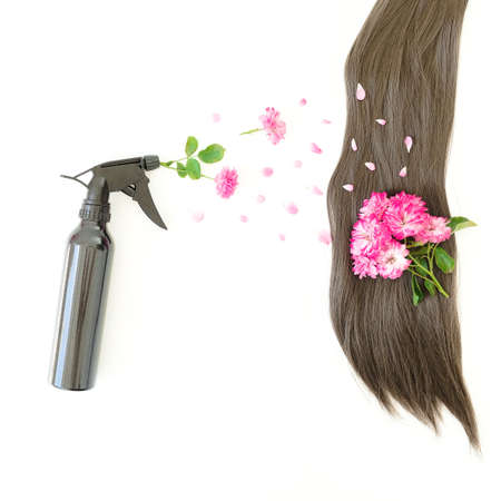 Beauty composition with hair styling spray and pink flowers on white background. Flat lay, top view