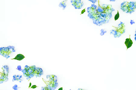Floral frame of blue flowers and leaves on white background. Flat lay. Floral background