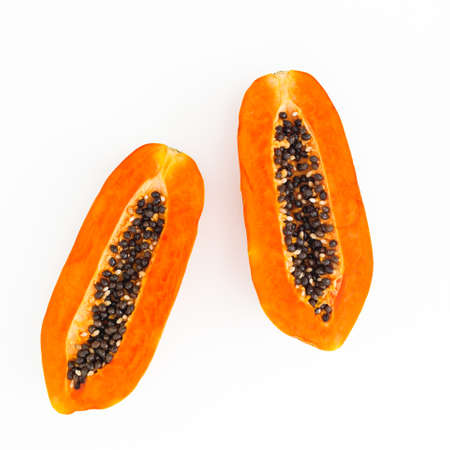 Two half of papaya fruit on white background. Flat lay. Top view. Banco de Imagens