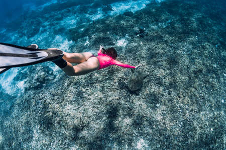 Freediver woman glides underwater with turtle in ocean. Snorkeling with green sea turtle.