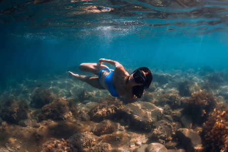 Freediver woman holding sand in hands underwater. Freediving in tropical blue ocean