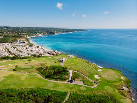Golf field and blue ocean in Bali. Aerial view of tropical island