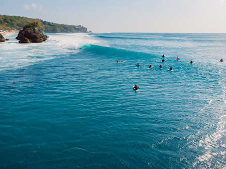 Surfers in blue ocean at Bali. Aerial view of tropical island with waves