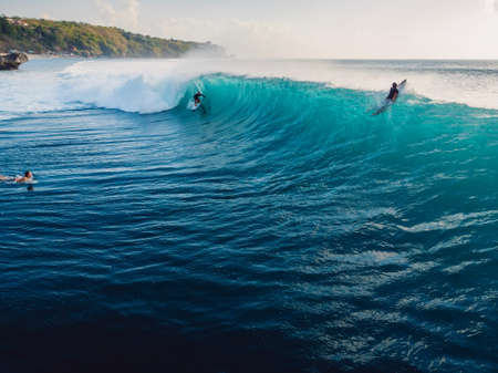 Aerial view with surfing on ideal barrel wave. Blue perfect waves and surfers in ocean Stock fotó