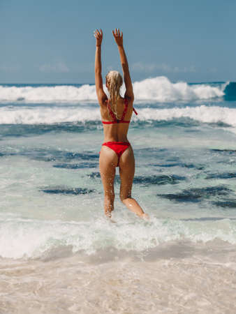 Attractive slim woman in bikini relax at beach in Bali. Caucasian model with ocean