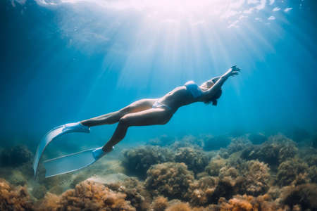 Freediver woman glides underwater with sand in hand. Free diver with fins posing underwater in transparent sea Stock fotó