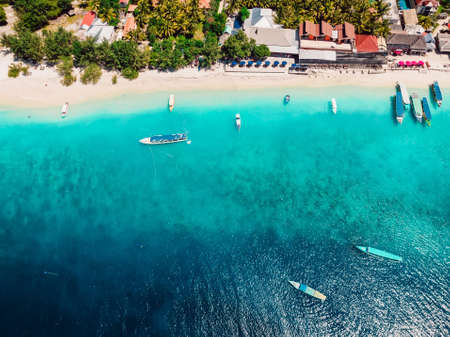 Tropical beach and transparent ocean with boats. Aerial view. Holiday resort