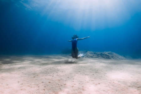 Lady freediver with fins posing and glides underwater in blue ocean with sunlight.