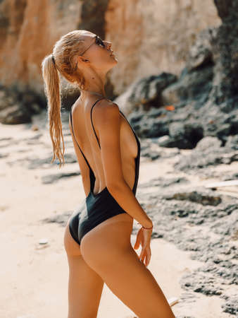 Sexy slim woman in bikini relax at beach in Bali. Caucasian model and ocean with waves