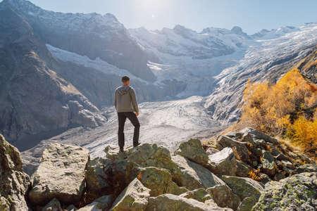 Hiker man at the crystal lake in autumnal mountains. Mountain lake and hiker traveler