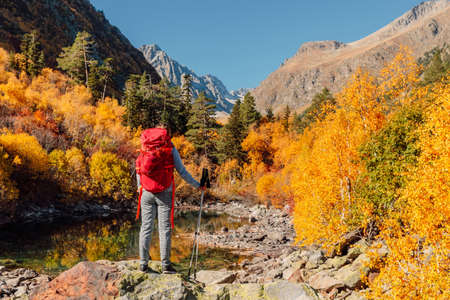 Hiker woman with backpack in the autumnal mountains. Mountain with glacier and hiker tourist