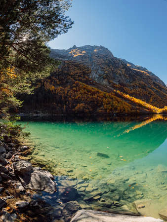 Mountain lake with clear water and sunlight. Mountains and lake