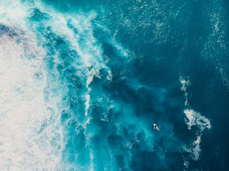 Blue ocean with waves and foam. Aerial view with surfer and sea background