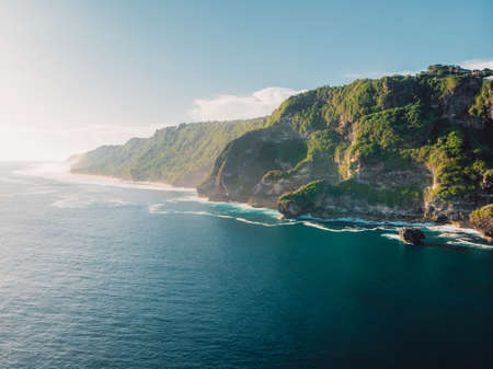 Amazing coastline with rocks, sunshine and ocean in Bali. Aerial view Stock Photo