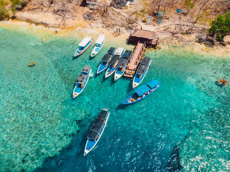 Touristic boats near the pier in blue transparent ocean at Menjangan island. Aerial view.