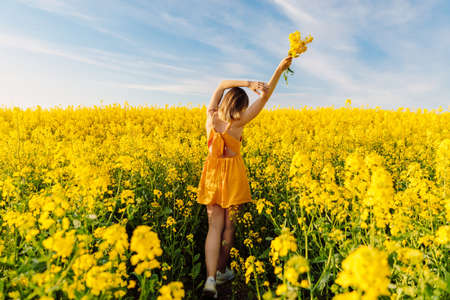 Attractive cheerful woman on rapeseed field with sunset light. Yellow flowers and happy woman