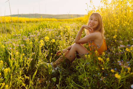 Portrait of woman on blooming yellow flowers with sunset light.