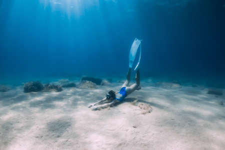 Free diver in swimwear underwater at the deep in ocean with sunlight.