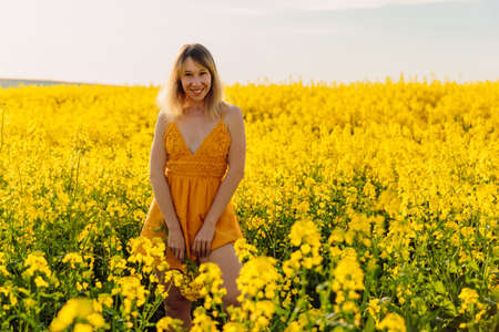 Attractive cheerful woman on rapeseed field with sunset light. Yellow flowers and happy caucasian woman