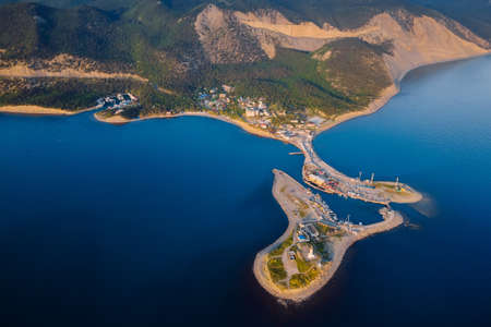 Aerial view of coastline with sea, mountains, canyon and lighthouse on island with sunset light