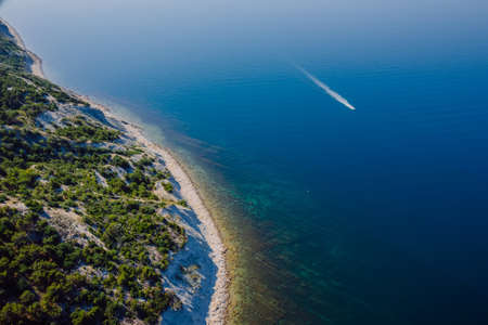 Coastline with blue sea, cliff with pine trees and motor boat. Summer day on sea. Aerial view