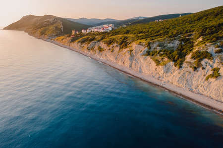 Aerial view of summer coastline with grass and blue sea. Coastline with sunset colors