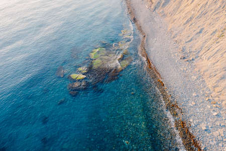 Aerial view of sea surface with stones and coastline