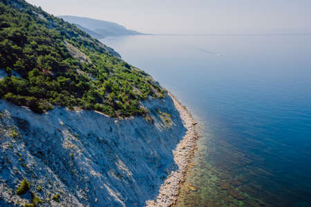 Coastline with blue sea and highest cliff with pine trees. Summer day on sea. Aerial view