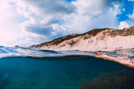 Split shot with coastline and underwater scene with sun rays and transparent sea water.