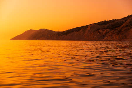 Bright sunset or sunrise at quit ocean with coastline with mountains