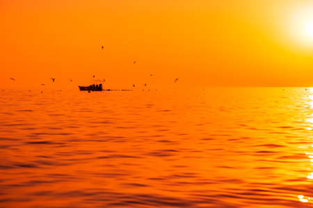 Bright sunset or sunrise at quit ocean with fishing boat and birds Foto de archivo
