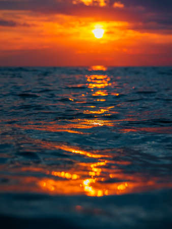 Sunset with clouds, warm colors and waves in ocean.