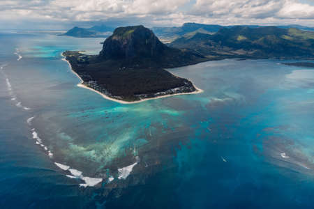 Tropical island with Le Morne mountain, blue ocean with waves and beach in Mauritius. Aerial view