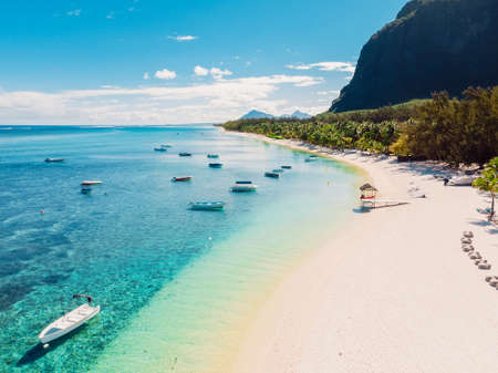 Luxury beach with mountain in Mauritius. Tropical beach with palms and ocean with boats. Aerial view