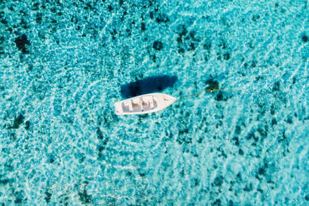 Boat in transparent blue ocean at tropical island. Aerial view.