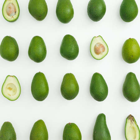 Avocado pattern on white background. Flat lay, top view. Food concept.