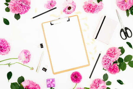 Flat lay work place with clipboard, pink flowers and accessories on white background. Flat lay, top view. Foto de archivo