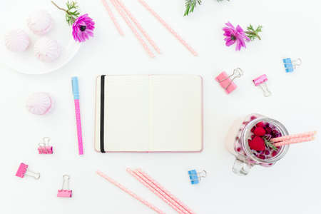 Smoothie with straws, marshmallow, anemones flowers and diary on white background. Flat lay.